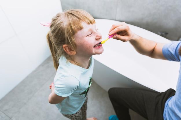 娘の歯を磨く穀物父 無料写真