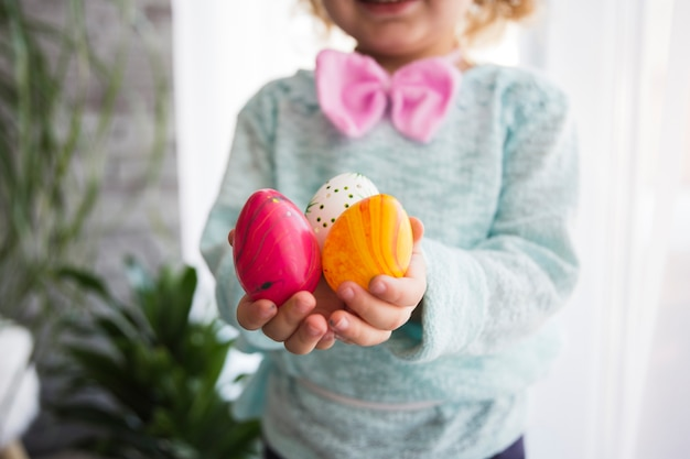 Crop girl showing easter eggs Free Photo
