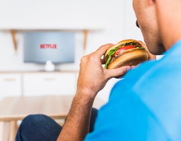 Crop guy eating hamburger and watching tv shows Free Photo