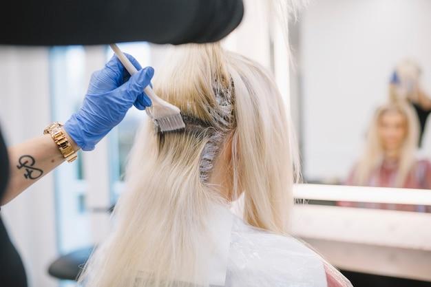Crop hairdresser applying chemical dye Premium Photo