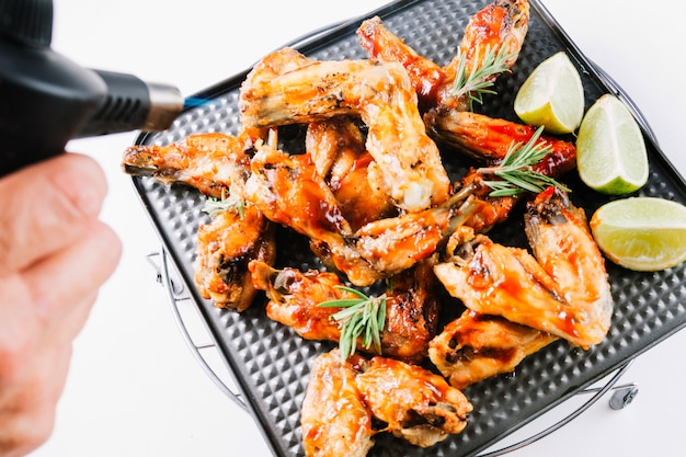 Crop hand blowtorching chicken wings Free Photo