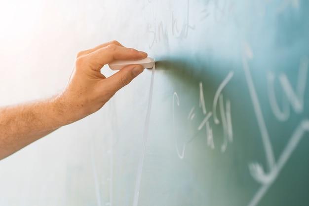 Crop hand chalking on blackboard Free Photo