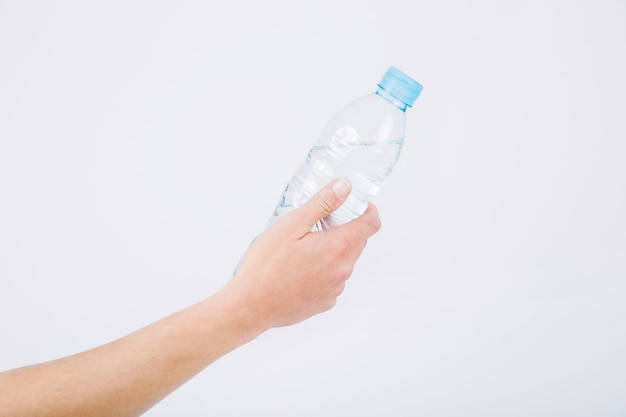 Crop hand holding bottle of water Free Photo