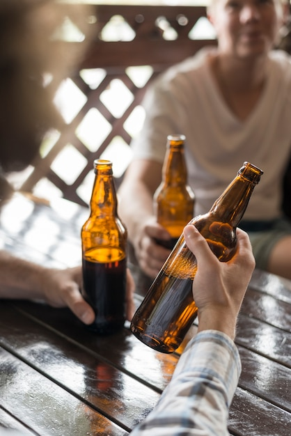 Crop hand holding cold beer near friends Free Photo