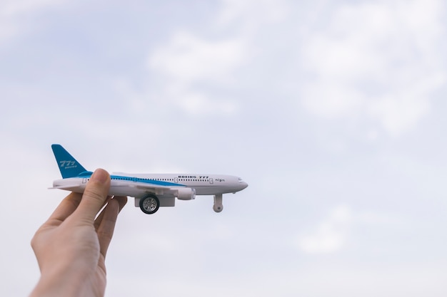 Crop hand holding toy airplane Free Photo