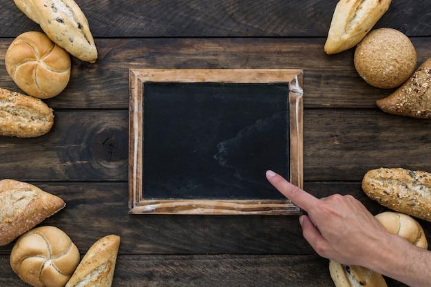 La mano del raccolto che indica alla lavagna vicino al pane Foto Gratuite