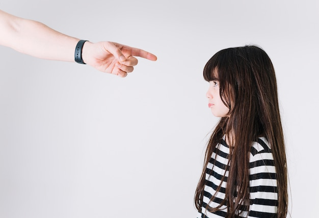 Crop hand pointing at upset girl Free Photo