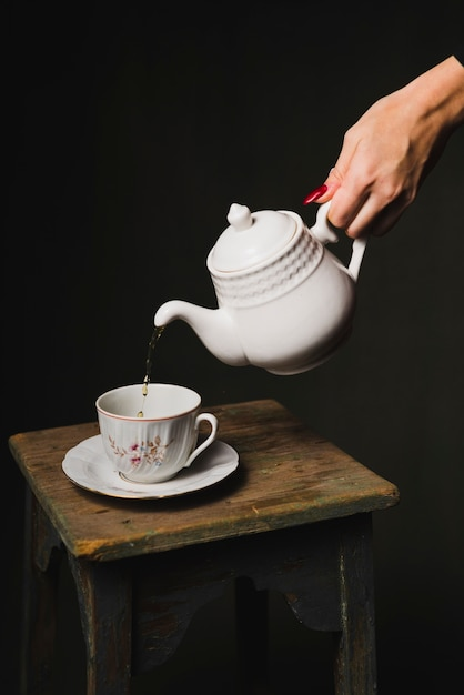 Crop hand pouring tea into cup Photo   Free Download