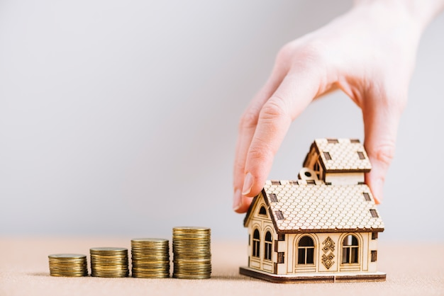 Crop hand putting house near coins Free Photo