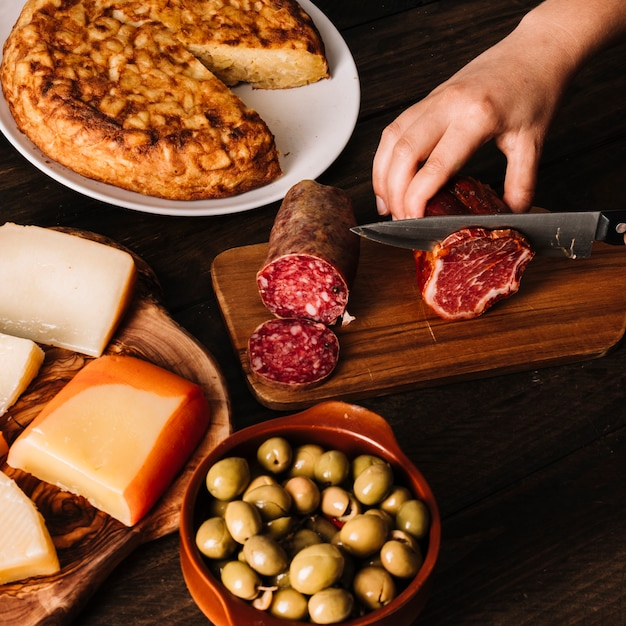 Crop hand slicing smoked meat near assorted food Free Photo
