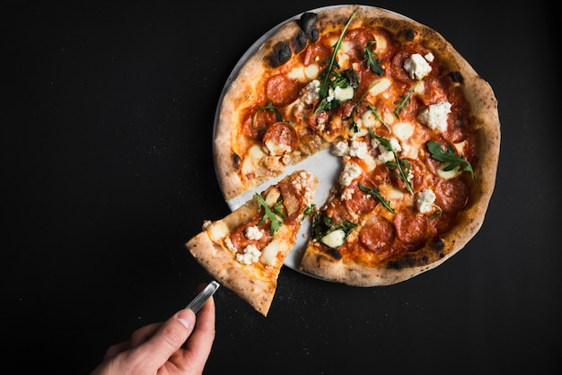 Crop hand taking piece of pizza