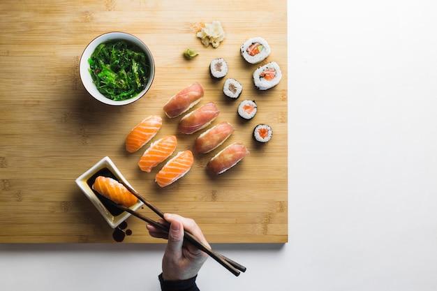 Crop hand taking sushi roll Free Photo