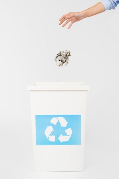 Crop hand throwing paper in bin Free Photo