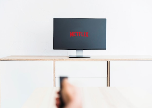 Crop hand using remote control on tv with netflix logo Free Photo