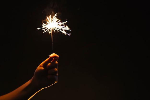 Crop hand with sparkler Free Photo