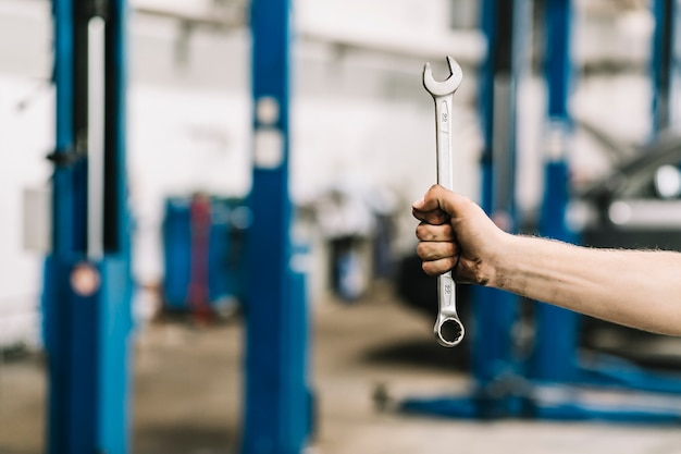 Crop hand with wrench in workshop Free Photo
