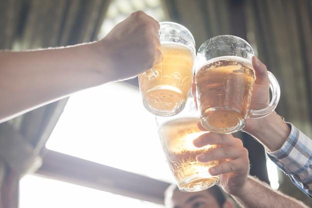Crop hands clinking mugs of booze in bar Free Photo