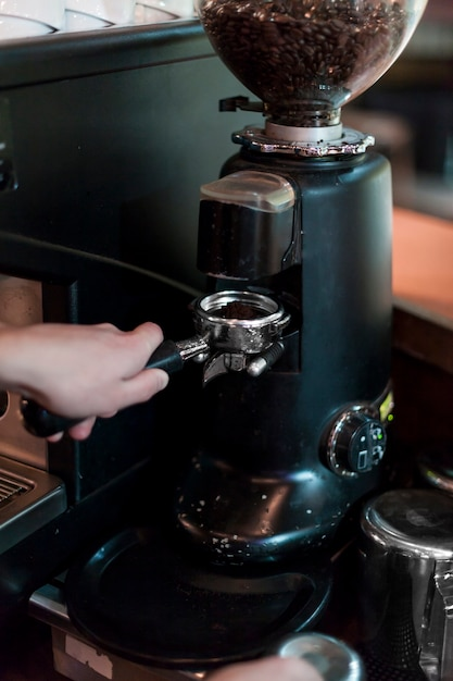 Crop hands grinding coffee into portafilter Free Photo
