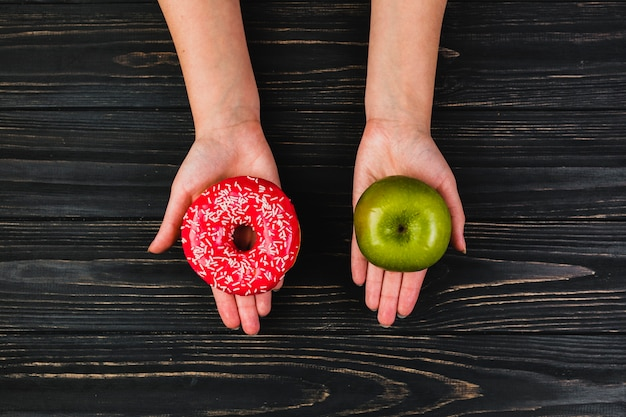 Crop hands holding donut and apple Free Photo