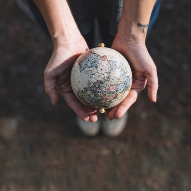 Crop hands holding globe Free Photo