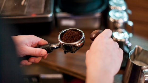 Crop hands holding portafilter with fresh coffee Free Photo