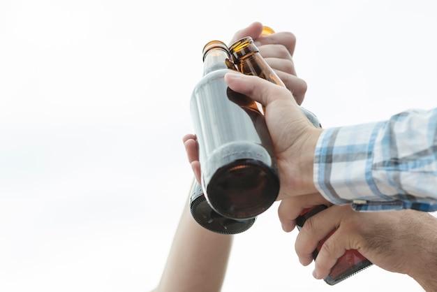 Crop hands of men clinking bottles of beer Free Photo