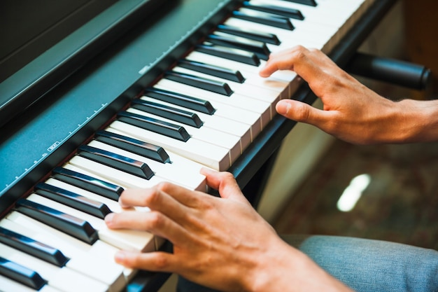 Crop hands playing electric piano Free Photo