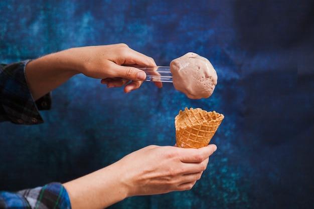 Crop hands putting ice-cream in cone Free Photo