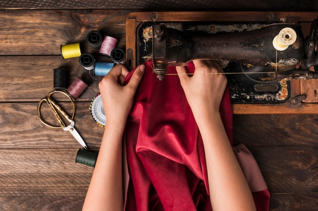 Crop hands sewing on machine Free Photo