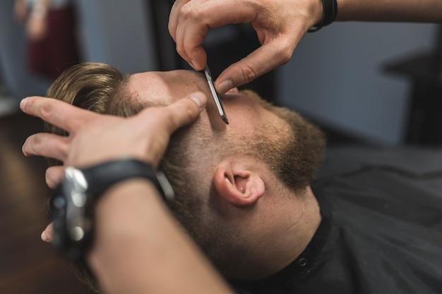 Crop hands shaving bearded man Free Photo