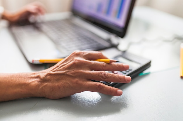 Crop hands using calculator and laptop Free Photo