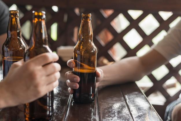 Crop hands with beer in pub Free Photo