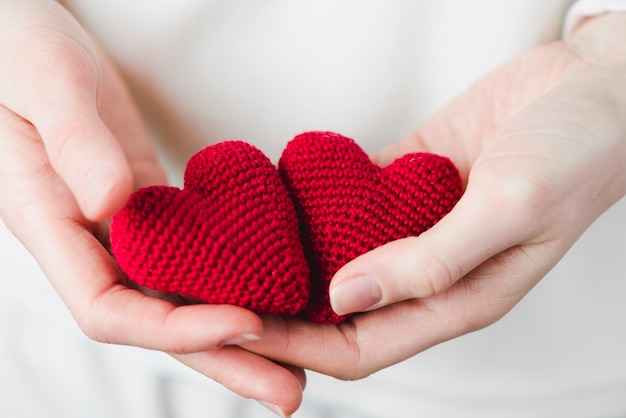 Crop hands with knitted hearts Free Photo