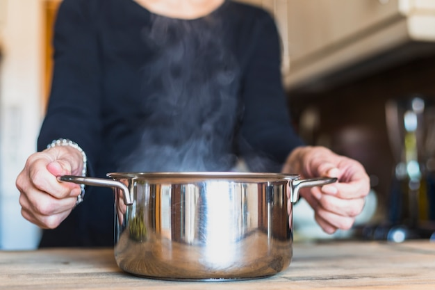 Crop hands of woman cooking dish in kitchen Free Photo