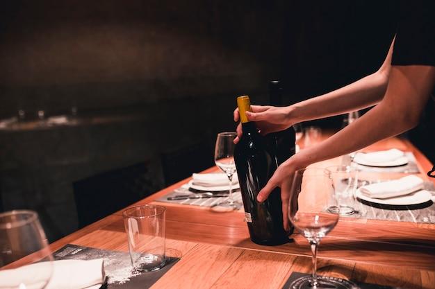 ワインをテーブルに置く作物のホステス 無料写真