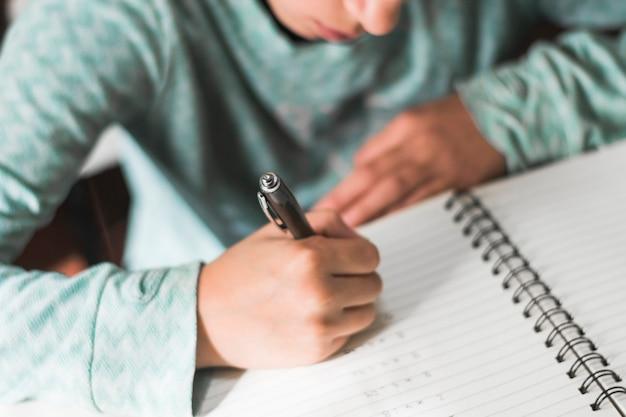 Free Photo   Crop kid writing in notebook