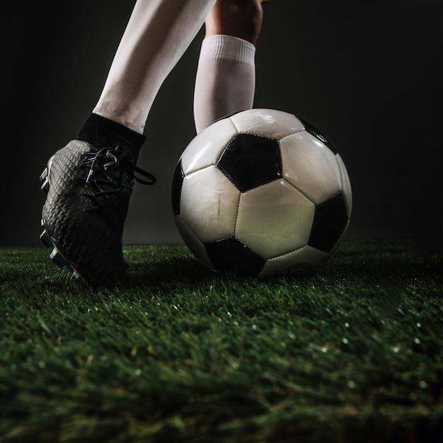 Crop legs kicking ball on grass Free Photo