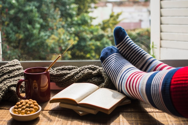 Crop legs near books and hot beverage Free Photo