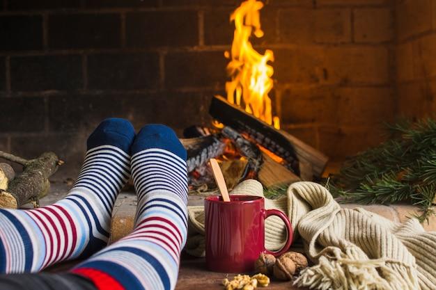 Crop legs warming near fireplace Free Photo