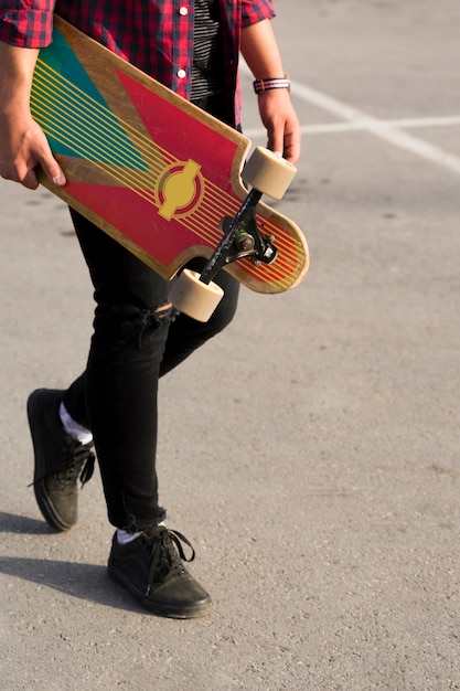 Crop longboard in hands of hipster Free Photo
