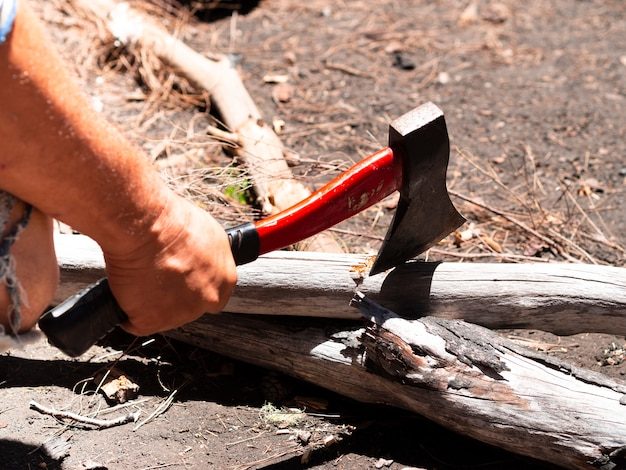 Crop male hand chopping wood with axe on sunny day Free Photo