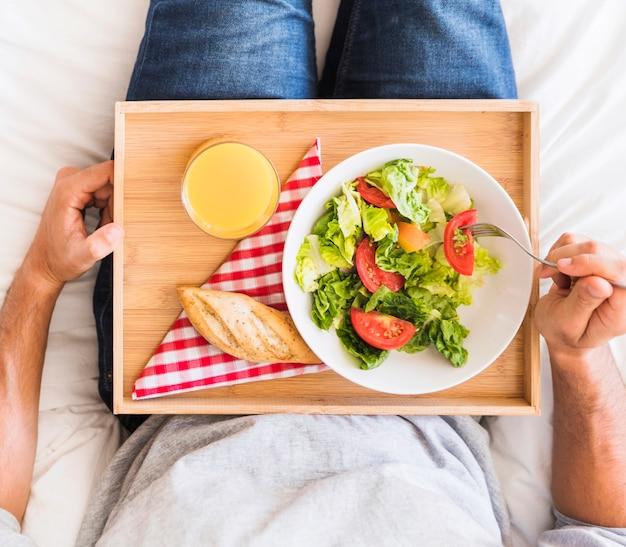 Crop man eating healthy food on bed Free Photo