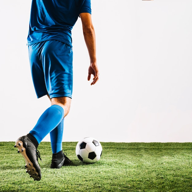 Crop man in blue uniform kicking ball Free Photo