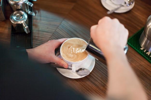 Crop man making tasty latte Free Photo