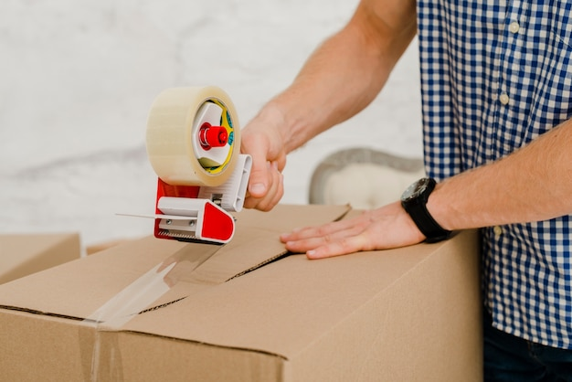 Crop man packing box with sticky tape Free Photo