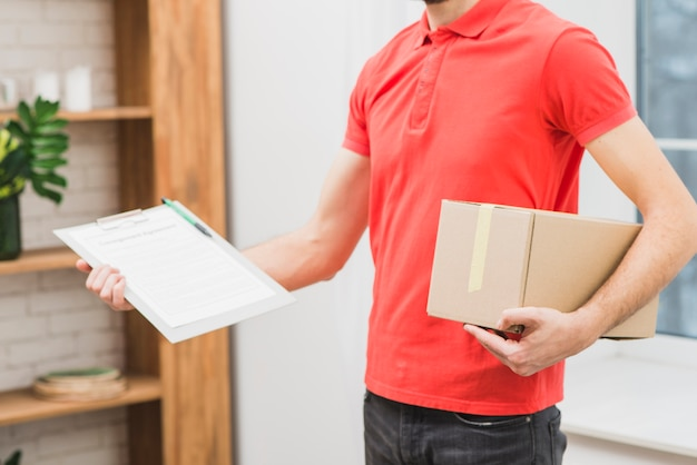 Crop man with clipboard and parcel Free Photo