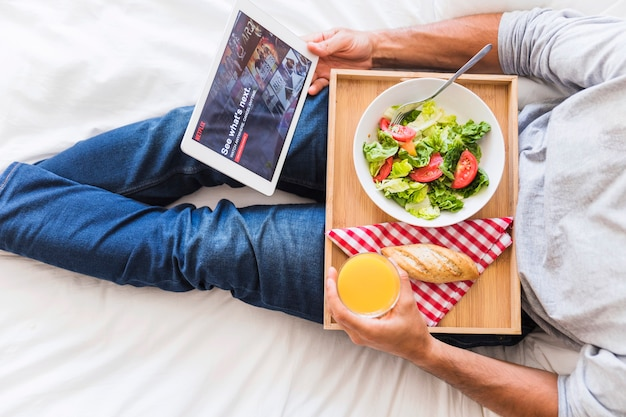 Crop man with healthy food browsing netflix site Free Photo
