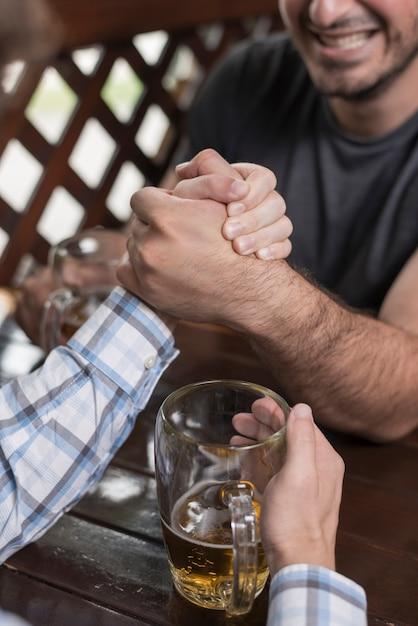 Crop men arm wrestling in bar Free Photo