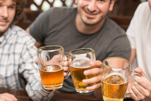 Crop men clinking mugs in bar Free Photo