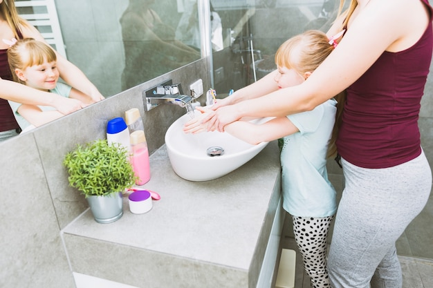 Crop mother helping daughter to wash hands Free Photo